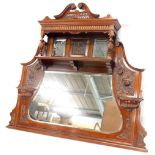 A late Victorian 20thC walnut overmantel mirror, with a swan neck pediment, above a carved frieze, a