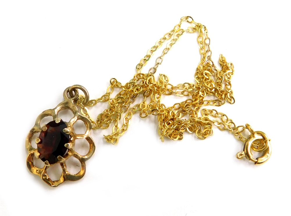 A 9ct gold pendant and chain, the floral pendant set with garnet in claw setting, on a fine link yel