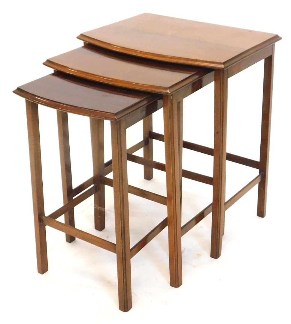 A nest of three mahogany D shaped tables, each with a moulded edge and plain supports, the largest 4