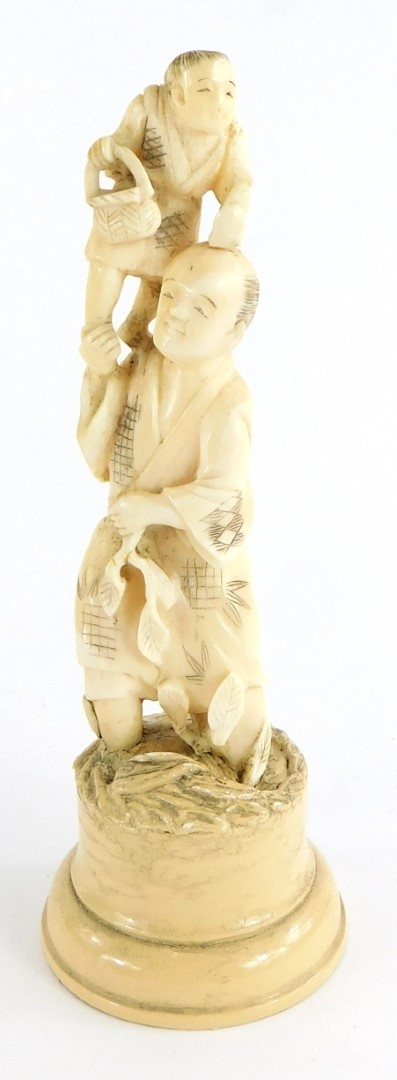 A late 19thC Japanese ivory Okimono, carved in the form of a gentleman with a young child on his sho