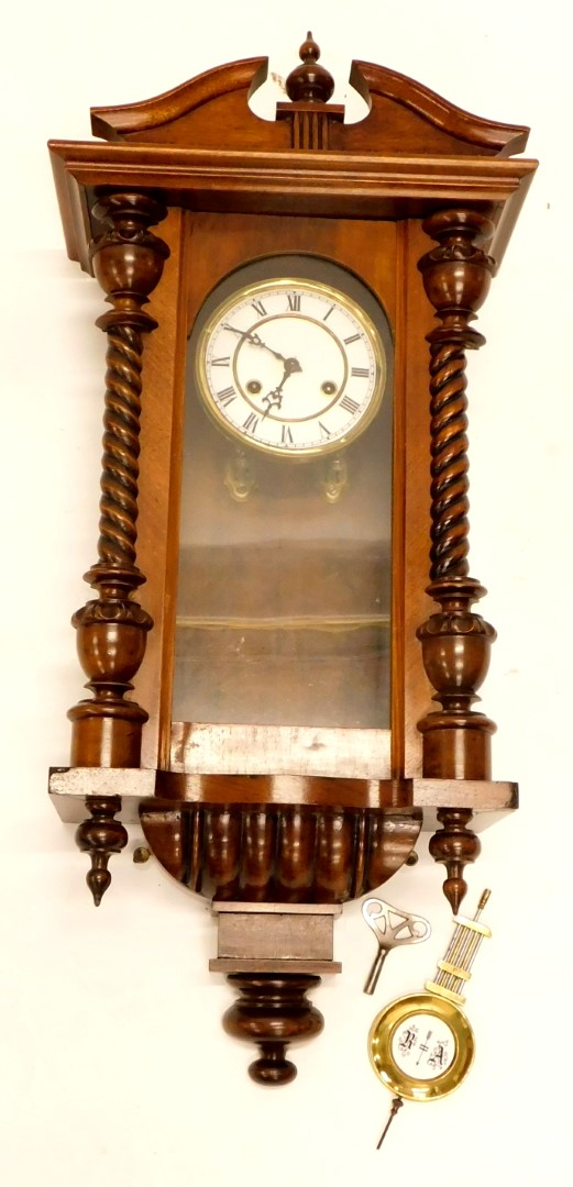 A late 19th/early 20thC Vienna wall clock, in a walnut case with a white enamel dial, 66cm long.
