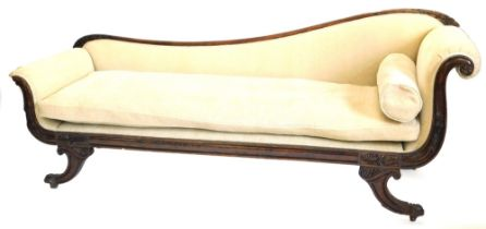 A George IV simulated rosewood show frame chaise longue, upholstered in beige fabric, carved with sc