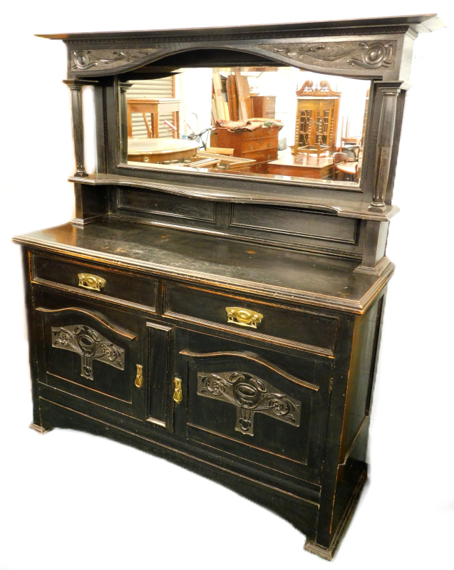 A late 19th/ early 20thC ebonised oak sideboard, the top with a carved crest, above a bevelled mirro