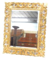A late 18th/early 19thC giltwood wall mirror, the frame carved with scrolls, leaves, etc., surroundi