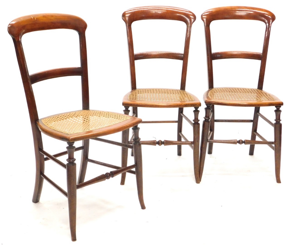 A set of three Victorian mahogany bedroom chairs, each with a caned seat on splayed legs.