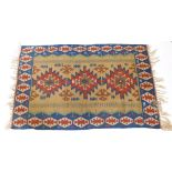An Eastern Turkish Kilim rug, with a typical geometric design in brown, red, blue and yellow, 109cm