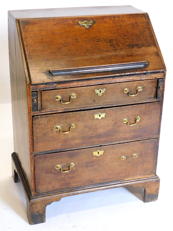 An 18thC oak bureau, the fall enclosing a fitted interior above three graduated drawers, each with b