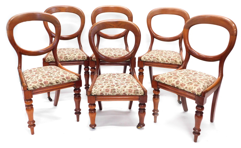 A set of six Victorian mahogany balloon back chairs, each with a drop in seat on turned legs, one re