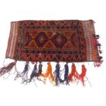 A Persian saddle bag, with a navy and red pole medallion, on an orange ground, 56cm x 110cm.