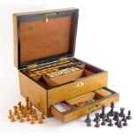 A 19thC oak games box or compendium, the hinged lid with a vacant oval cartouche enclosing bone and