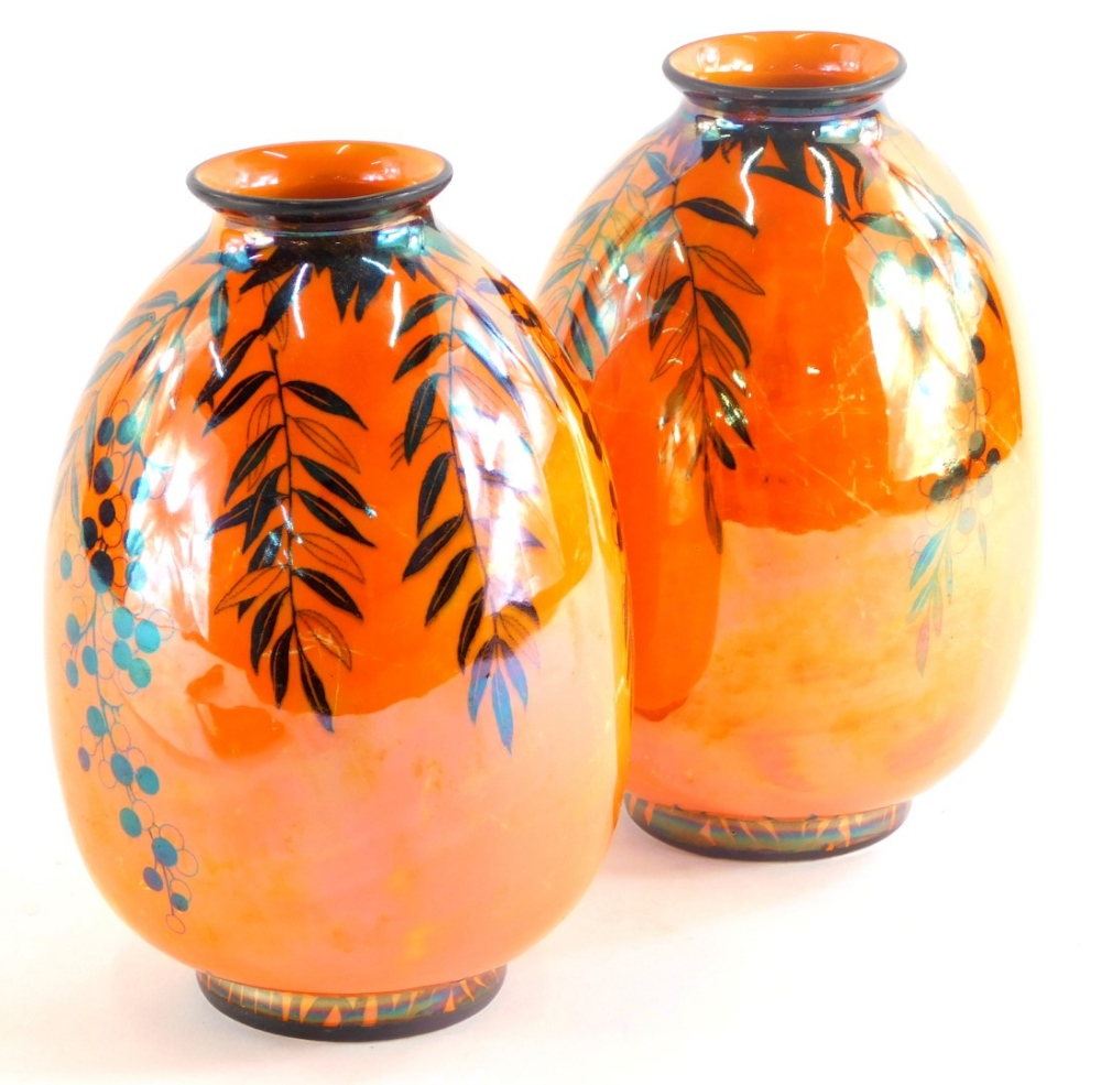 A pair of Crown Ducal lustre vases, each decorated with flowers and leaves in black on a vivid orang