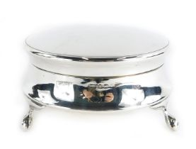 A George V silver trinket or powder box, with a plain circular hinged lid, on claw and ball feet, Bi