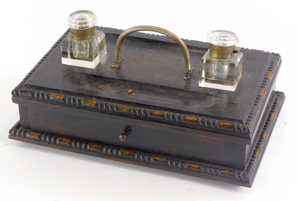 An early 20thC stained oak ink stand, with two square section glass wells, handle and a drawer, 29cm