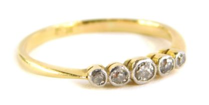 A five stone diamond dress ring, with five tiny diamonds, in rub over platinum setting, on a yellow