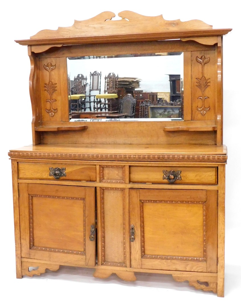 A late 19thC oak sideboard, the mirrored back with a shaped cornice, leaf carving and shelves, the b