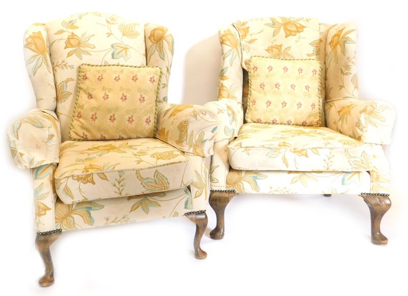 An associated pair of mahogany wingback chairs in George III style, each upholstered in gold and tur