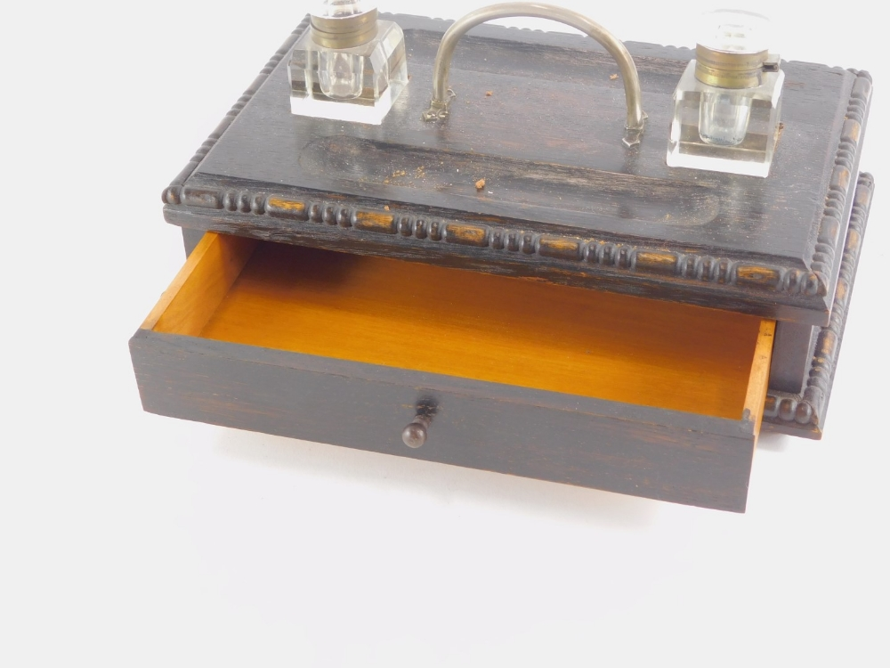 An early 20thC stained oak ink stand, with two square section glass wells, handle and a drawer, 29cm - Image 2 of 2