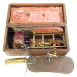 A Victorian improved Magneto-electric machine, mainly brass in mahogany case, 26cm wide.