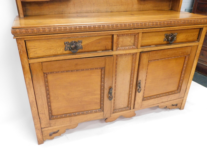 A late 19thC oak sideboard, the mirrored back with a shaped cornice, leaf carving and shelves, the b - Image 2 of 2