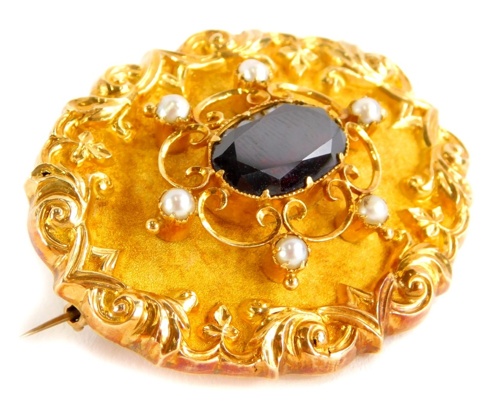 A Victorian yellow metal memorial brooch, of oval form set with a central garnet, flanked by seed pe