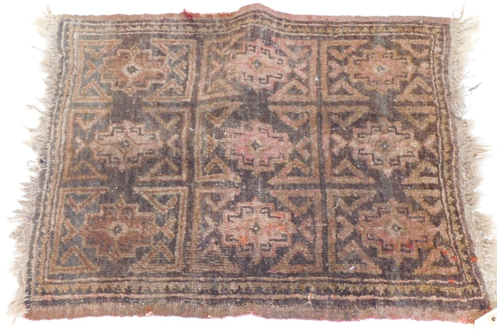A small Turkish or Afghan mat, with a design of nine medallions, in red, on a brown ground, (AF), 55