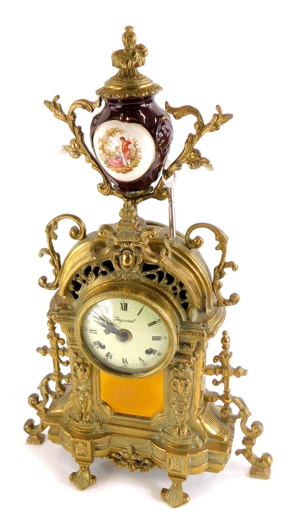 A Continental mantel clock, the rococo shaped cast brass case decorated with scrolls, the dial stamp