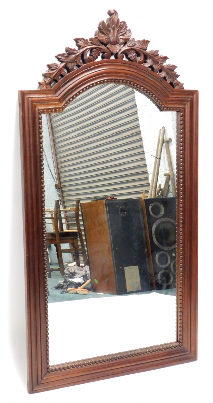 A mahogany wall mirror, with a leaf carved pierced crest, above a reeded arched frame, 147cm high, 7