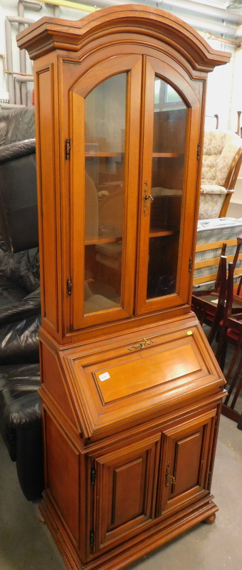 A hardwood bureau bookcase, the top with two glazed doors above a fold over flap, and two hinged doo
