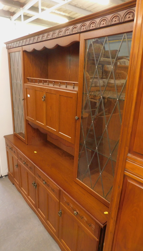 An oak Morris Furniture Company dresser, the top with two leaded glazed doors, with a central flap s