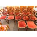 A set of twelve wheel back dining chairs, with red velvet seats. The upholstery in this lot does not