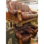An oak framed three seater sofa and two matching armchairs, in maroon leather fabric. The upholstery