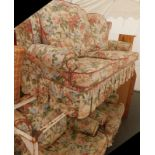 A three seater sofa, and two matching armchairs, in profusely decorated floral fabric.