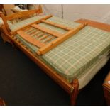 A pair of pine single beds, comprising headboards, slats, and two single mattresses.