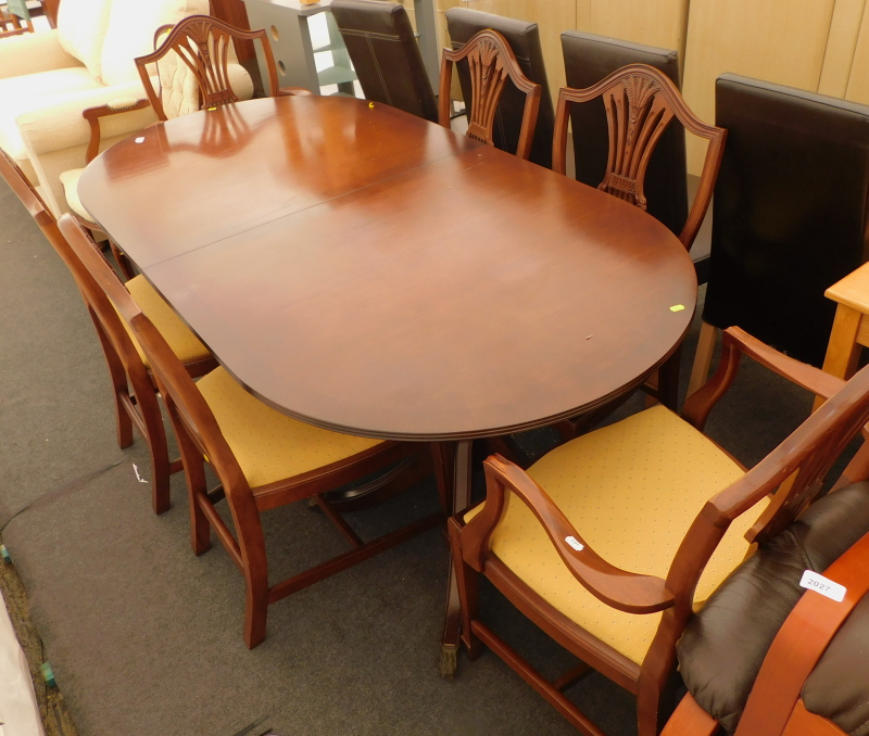 A mahogany twin pedestal extending dining table, and six Hepplewhite style chairs, with drop in seat