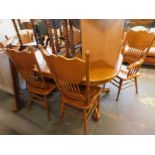 An oak extending dining table, with an associated set of six American style dining chairs.