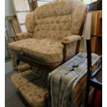 A pair of oak framed two seater sofas, in floral decorated fabric, and a folding bed.