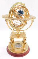 A brass orrery, with an astrological plate, raised on four supports above a table type base on three