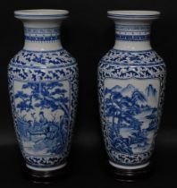 A pair of Chinese porcelain baluster vases, having blue and white landscape decoration, 54cm high wi