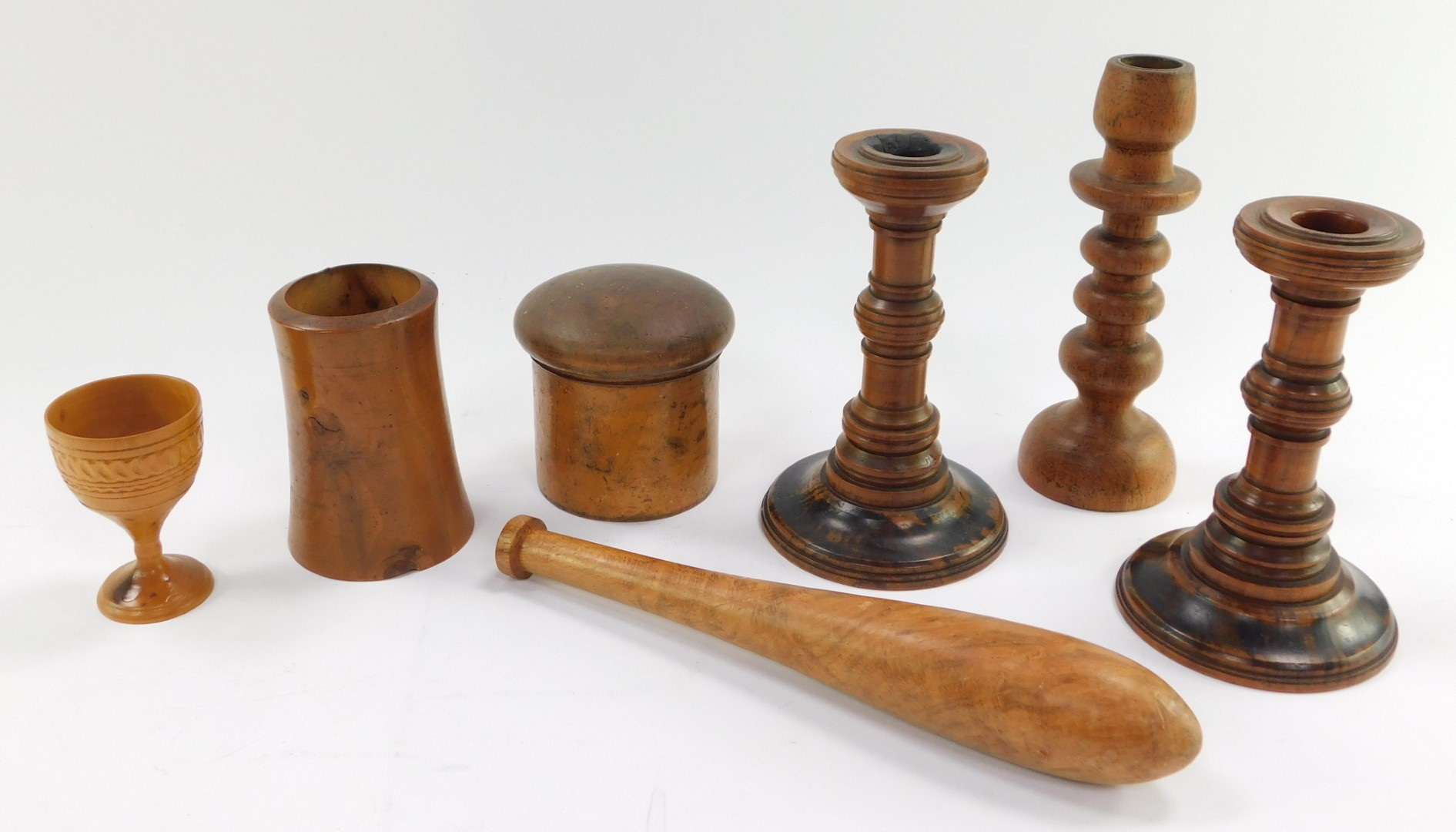 A group of treen, comprising a circular spice box and cover, three candlesticks, tapering vase, egg