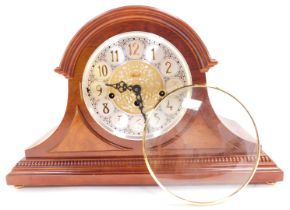 A Franz Hermle mahogany cased mantel clock, circular silvered dial bearing Arabic numerals with cent