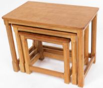 A Robert Thompson of Kilburn 'Mouseman' nest of three oak tables, bearing carved mouse to a leg of e