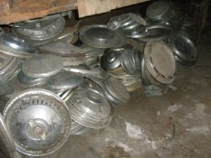 A large quantity of metal hub caps and wheel trims for classic cars, to includ Mercedes, Trimuph, Wo