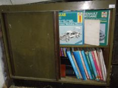 A large collection of Haynes manuals, in a wooden cabinet, plus a further selection currently housed