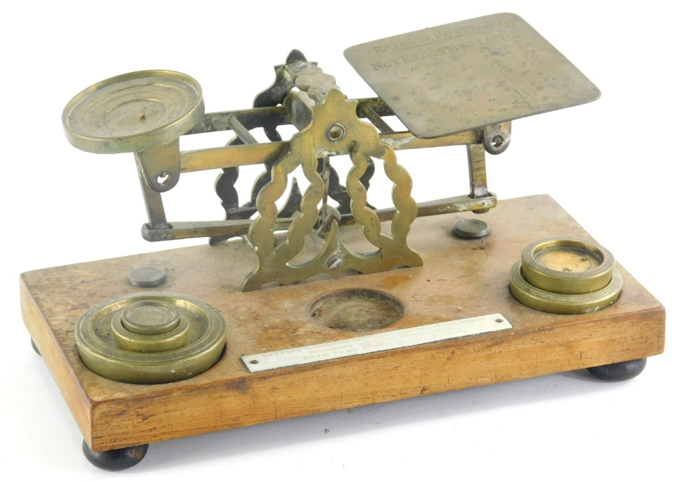 A set of early 20thC miniature brass table scales, with some weights, 23cm wide.