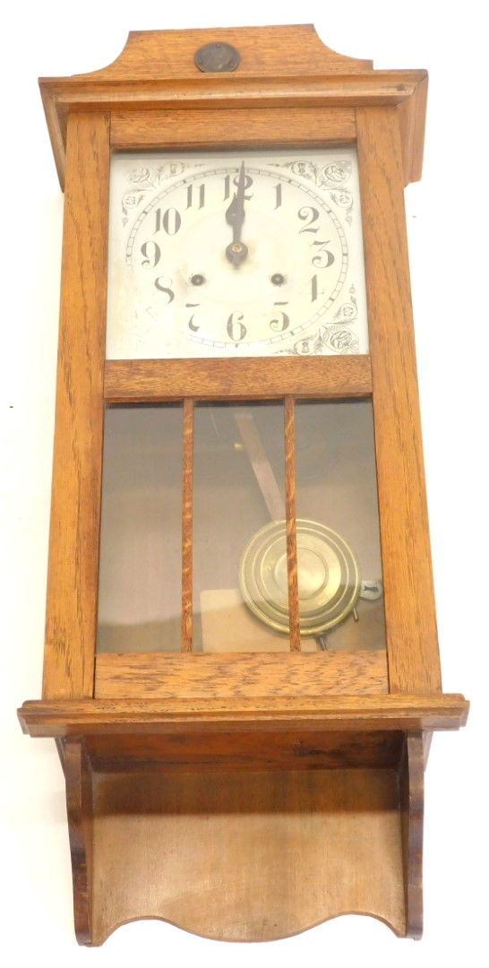 An early to mid 20thC oak wall clock, with silvered dial, 80cm high.