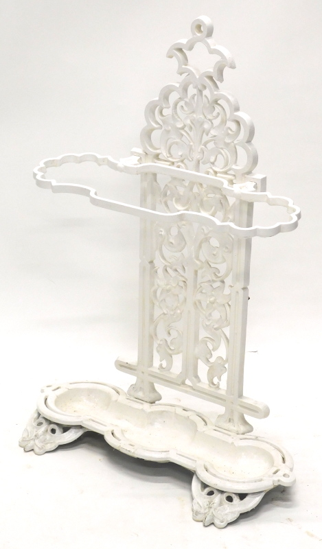 A Victorian style cast iron umbrella stand, with three apertures decorated with leaves, scrolls, etc