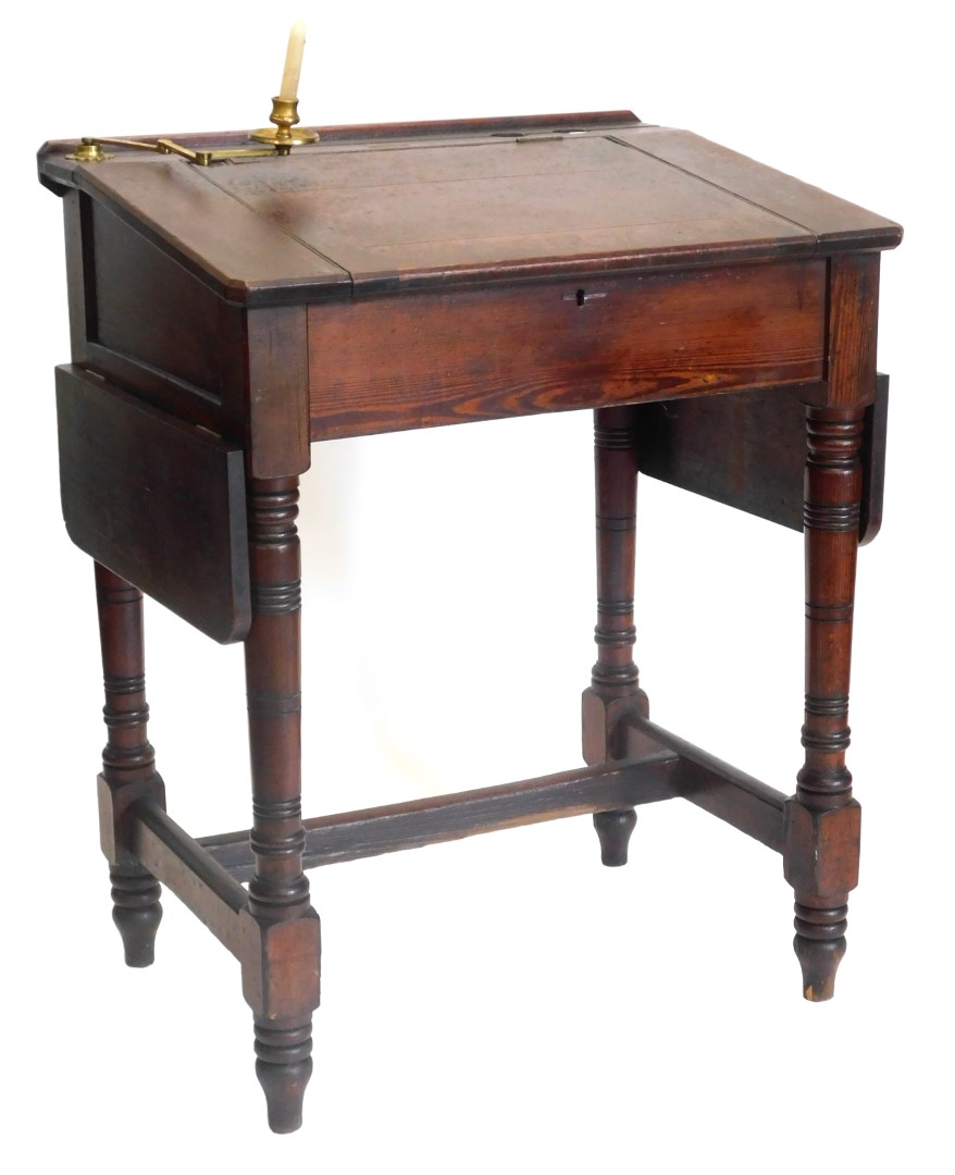 A Victorian pitch pine clerks desk, the sloped top with recess for inkwell and a adjustable candle s