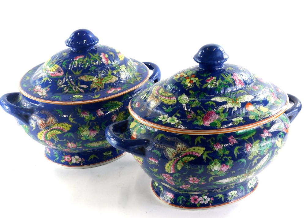 A pair of late Chinese porcelain two handled tureens and covers, each decorated in familie rose pale