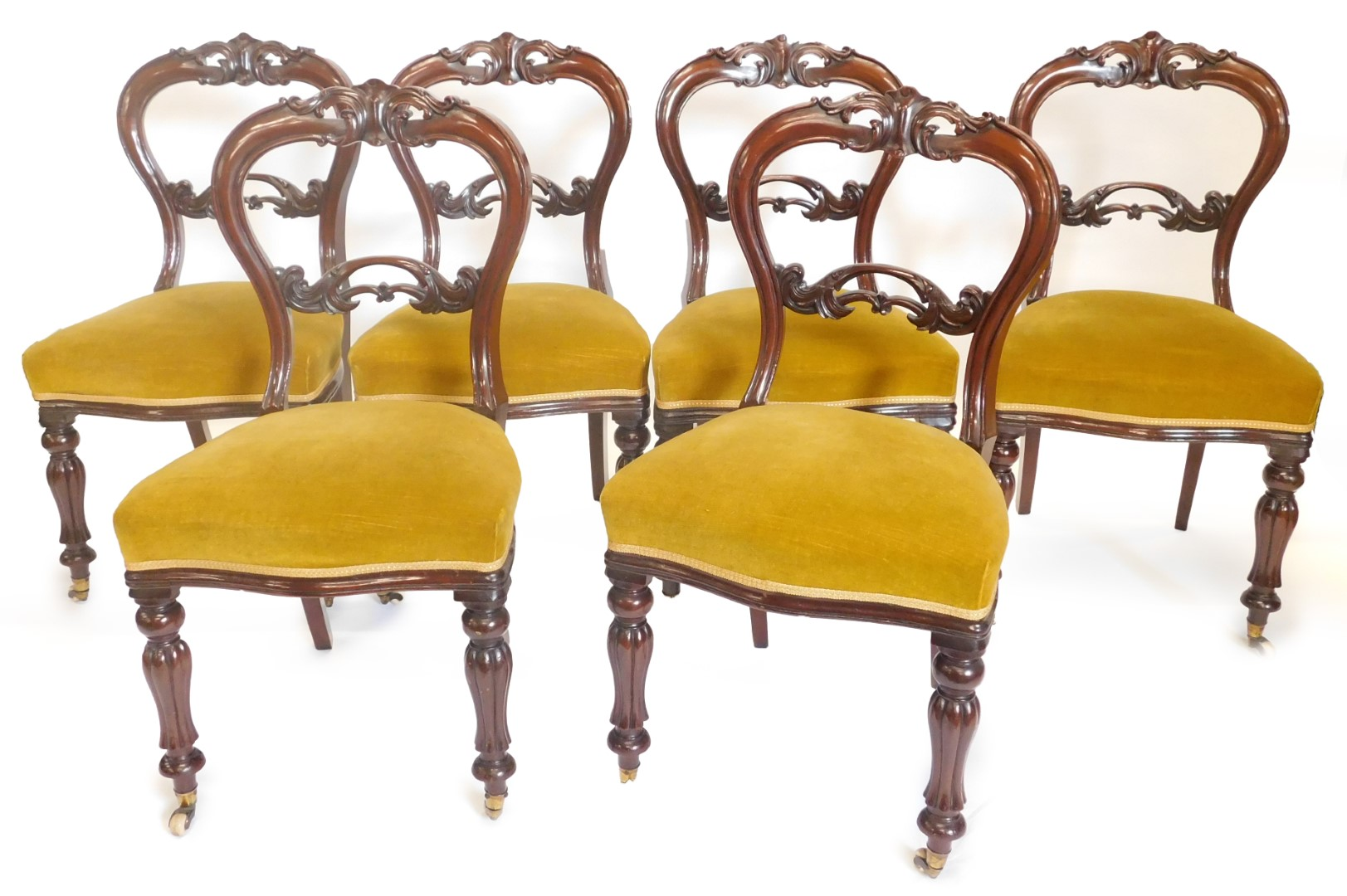 A set of six early Victorian mahogany balloon back chairs, each with a shaped carved and pierced bac