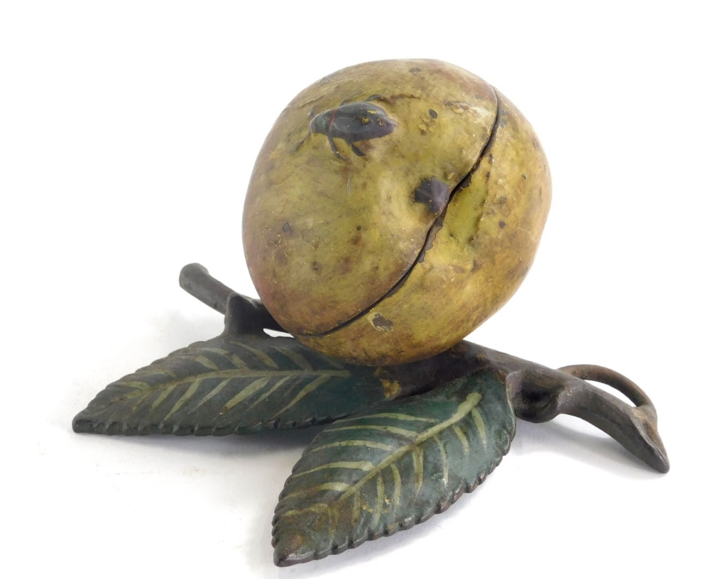An early 20thC cold painted metal money box, modelled in the form of an apple with a beetle and leaf